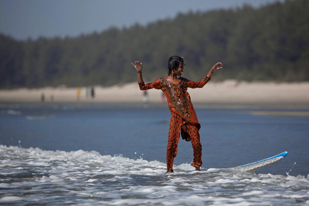 Johanara surfs during a break from selling chips on the beach in Cox's Bazar.