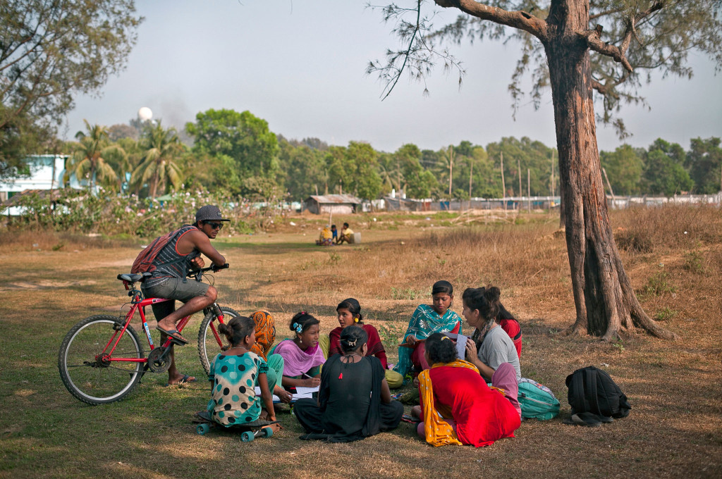 Rashed, the head of the Cox's Bazar Surf Club, watches as his wife, Venessa, tutors the surf girls in a park near the beach.