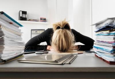 Businesswoman resting head on desk